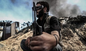 A fighter from the Jaish al-Islam sits near smoke billowing on the front line in the village of Tal al-Siwan area of the rebel-held stronghold of Douma.