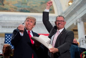 US President Donald Trump holds up a pen after signing the hat of Bruce Adams, chairman of the San Juan County Commission, after signing a presidential proclamation shrinking Bears Ears and Grand Staircase-Escalante national monuments at the Utah State Capitol in Salt Lake City, Utah.