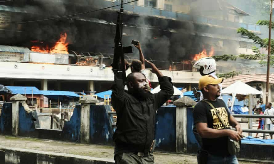 A police officer raises his rifle as the local market is seen burning during a protest in Fakfak, Papua province, Indonesia on 21 August.