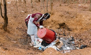 Cleaner Mbaruku.K. Nduhuye carries waste from Nyarugusu Dispensary which is dumped in an open pit for burning