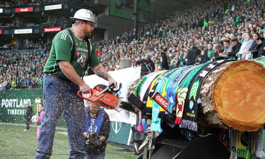 Mascot Timber Joey cuts a slice of the Timbers log after a goal.