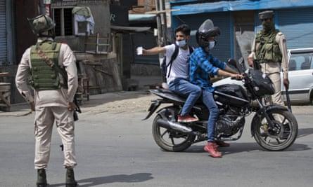 A Kashmiri man shows his ID card to soldiers during a curfew in Srinagar.