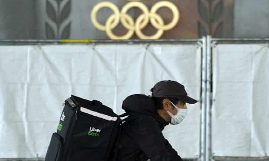 A courier rides near the Japan National Stadium in Tokyo