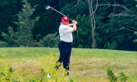 Trump golfs at his course in Sterling, Virginia.