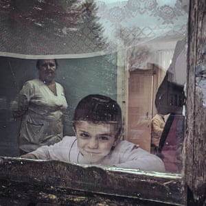 Young boy smiling through window.