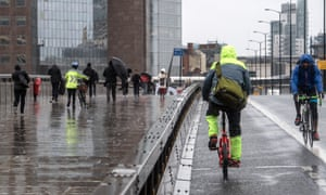 Cyclists and pedestrians alongside a security barrier on London Bridge