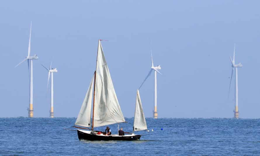 sailing boats pass an offshore windfarm