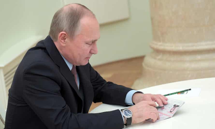 Putin holds the passport before handing it to Seagal.