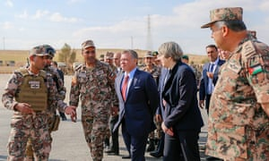 King Abdullah II of Jordan (centre) talking to Theresa May during their visit at a military base, near Amman, Jordan, earlier today.