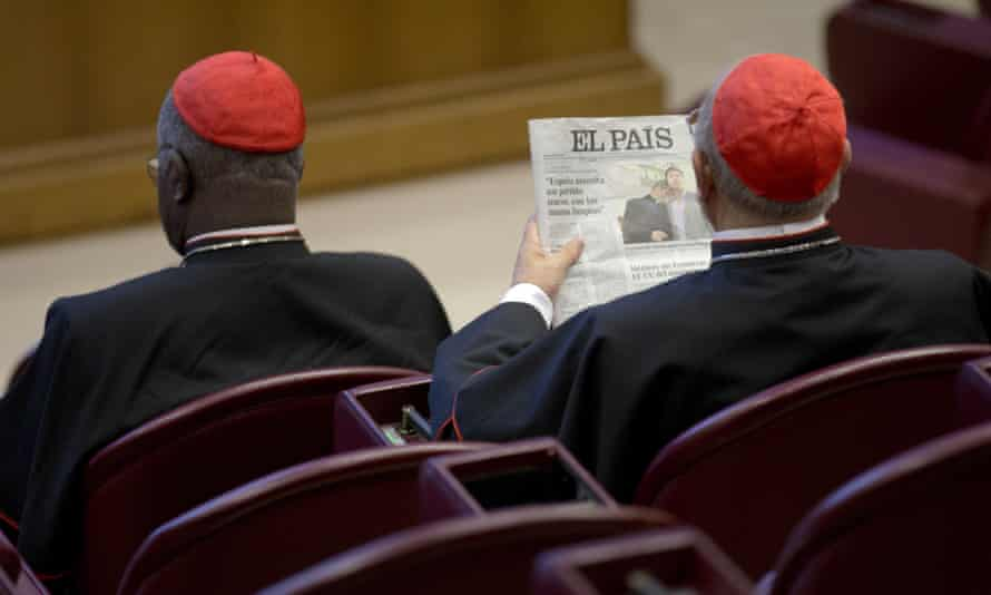 Spanish cardinal Ricardo Blázquez Pérez reads a newspaper showing a picture of Krzysztof Charamsa and his partner Eduard before the start of the morning session of the synod of bishops on family issues, at the Vatican.