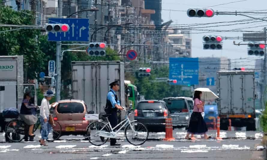 Pedestrians cross a street in Tokyo during this week's heatwave in Tokyo