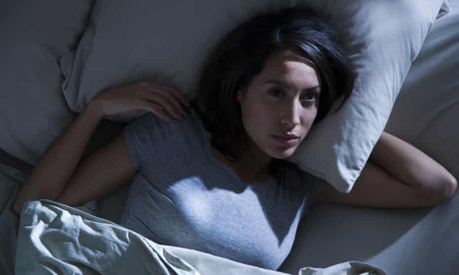 Woman lying awake in bed  in the dark