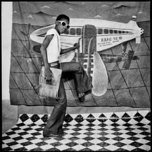A young man pretends to board a plane painted onto a backdrop. Autoportrait au Miroir by Sory Sanlé (1966)