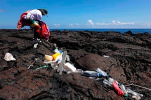 A volunteer collects waste on the shore of Isabela Island in the Galapagos Archipelago in the Pacific Ocean, off the coast of Ecuador
