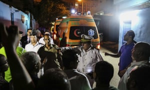 Egyptian police officers direct people as ambulances carry victims of an incident in which Egyptian forces mistakenly opened fire on tourists in the western desert last year.