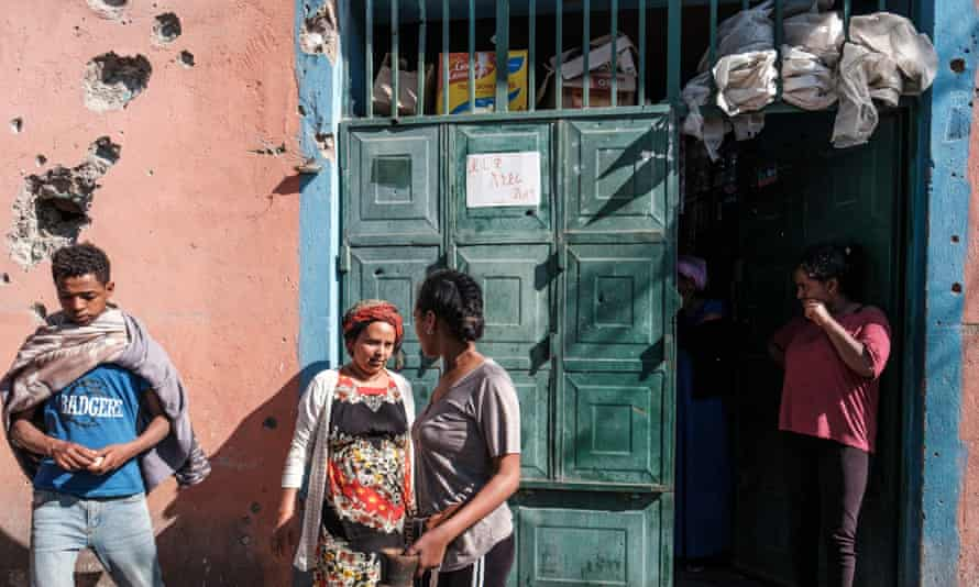 People stand outside a shop in Mekelle that was damaged in shelling when federal troops retook the town in November