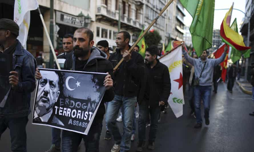 Kurdish demonstrators holding placards march during a protest against the Turkish president's Athens visit.