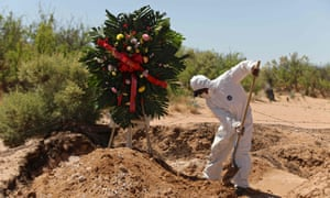 A cemetery worker covers the grave of a woman in an area of the San Rafael municipal pantheon designated for victims of the novel coronavirus, Covid-19, in Ciudad Juarez, Chihuahua State, Mexico, on 17 May 2020.