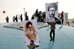 Two boys hold up posters of the Iranian supreme leader, Ayatollah Ali Khamenei, and the late revolutionary founder Ayatollah Khomeini