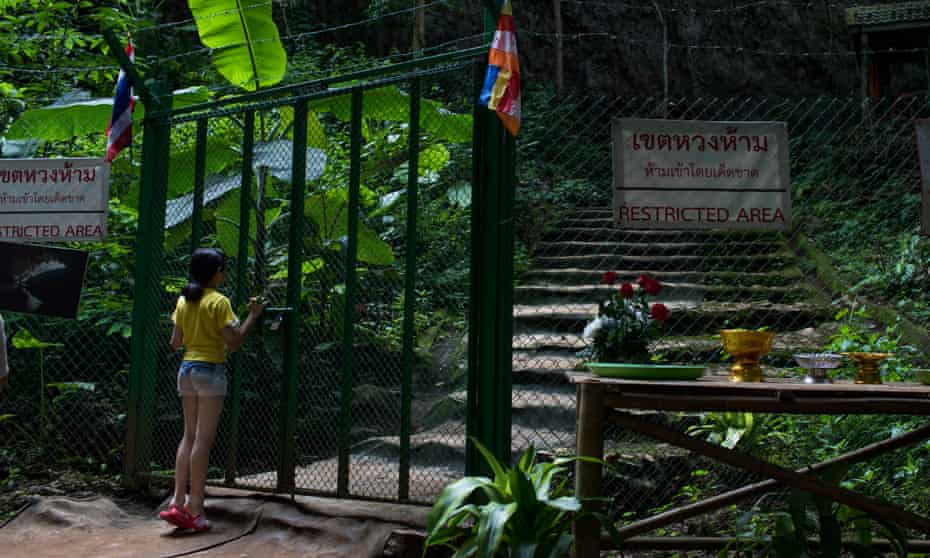 A visitor peers into the blocked entrance to Tham Luang Nang Non Cave, where 12 boys and their coach were trapped for 18 days