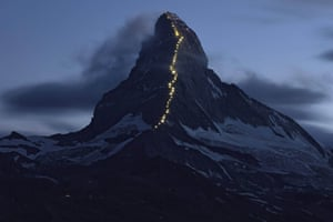 Solar powered lights are photographed along the Hoernli ridge on the Matterhorn in Zermatt, Switzerland. The first ascent of the mountain on the Hoernli ridge was made by Briton Edward Whymper one hundred and fifty years ago, on 14 July 1865, with six roped team members. The red light, fourth from top, marks the point where four men fell to their death on their descent of the North face.
