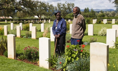 Eusebio Mbiuki and Gershon Fundi, two veterans of Britain's King's African Rifles, pay their respects to fallen comrades at a war graves cemetery near Mount Kenya.