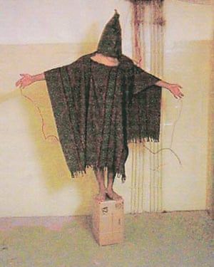 A hooded Iraqi prisoner is photographed standing on a box with wires attached to his left and right hand at the Abu Ghraib prison near Baghdad, Iraq, in November 2003. This photograph, taken by Staff Sgt. Ivan Frederick, is one of many showing the torture and abuse of detainees held by US forces.