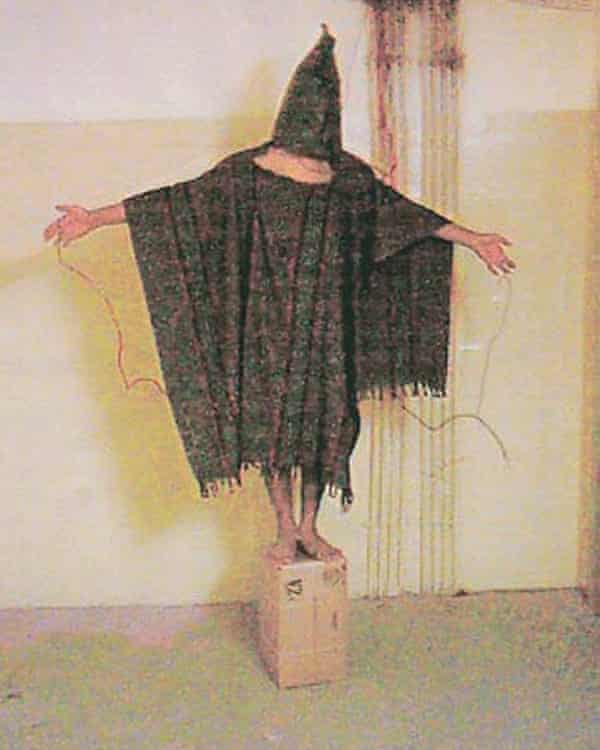 a hooded and wired Iraqi prisoner in the Abu Ghraib prison.