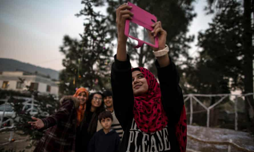 Young Muslims take a selfie in front of a Christmas tree in a Christian slum in Islamabad, Pakistan.