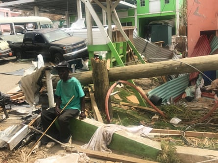 A man sits among wrecked buildings in Tortola.