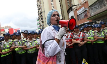 A woman shouts slogans in front of police during a rally of health workers and opposition supporters, amid a shortage of medical supplies.
