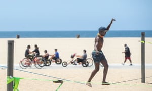 Young people relax at Santa Monica Beach on Monday as Los Angeles county is expected to reach the milestone of 100,000 coronavirus cases.