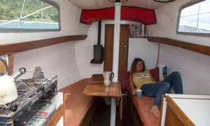 Susan Smillie reading a book, lying in the cabin of her boat
