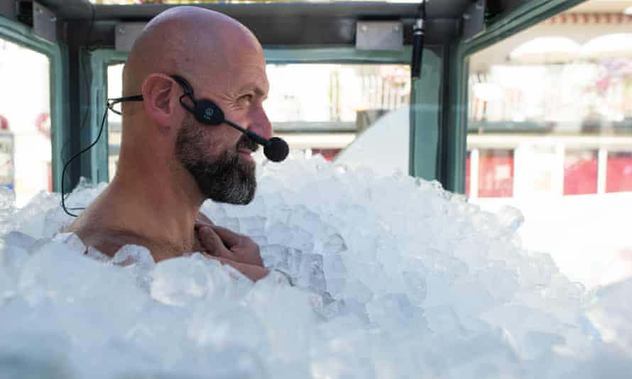 Josef Koeberl stands in a glass box filled with ice