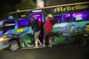 Touts hang dangerously on the door of a moving matatu as they pick passengers during rush hour