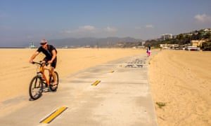 A man rides a bike on a cycle path across a beach in Los Angeles.