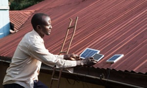 Placing solar panels on roof of house to charge, Longisa, Bomet district, Kenya