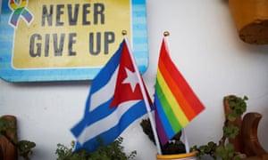 A couple displays a Cuban flag and a Pride rainbow flag in Havana.