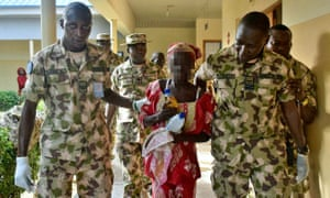 Amina Ali Nkeki with Nigerian soldiers after her escape.