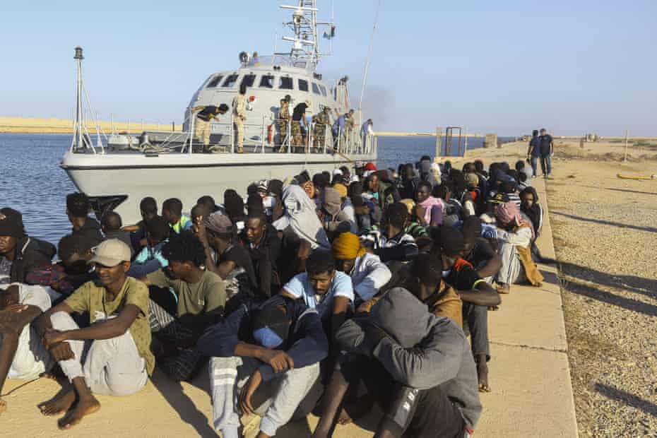Rescued migrants next to a coastguard boat in Khoms, east of Tripoli, last month.