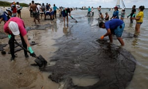 Environmental volunteers work to remove oil waste from Suape Beach, in Cabo de Agostinho, state of Pernambuco, Brazil.