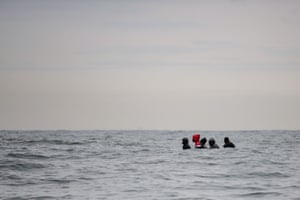 Migrants sit onboard a boat navigating waters between Sangatte and Cap Blanc-Nez in the English Channel off the coast of northern France.