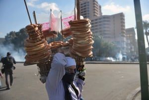 An Egyptian street vender sells bread as police fire teargas during clashes with protesters near Cairo's Tahrir Square in 2013