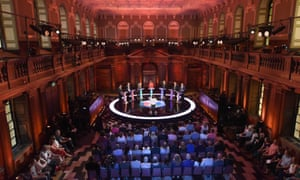 Seven candidates debate in front of a studio audience.