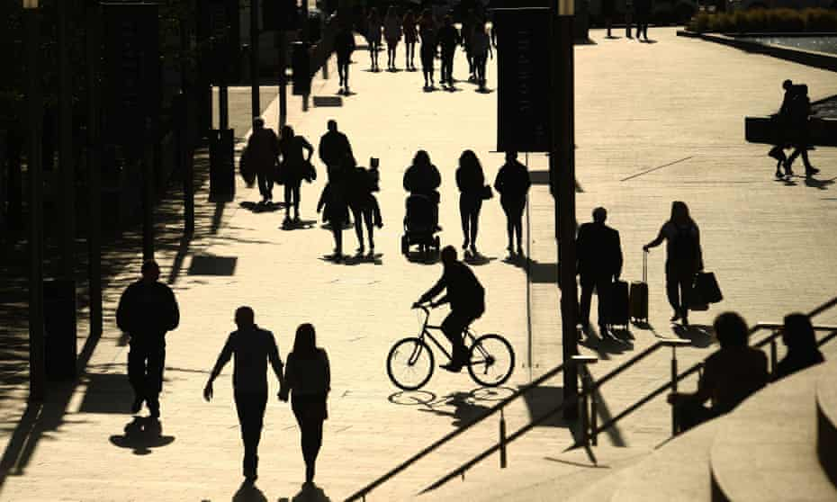 People are silhouetted against the late summer sun in Liverpool city centre last month.