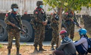 سربازان از معترضانی که هنگام بستن جاده ای در نزدیکی زندان در نایپیداو بازداشت شده اند ، نگهبانی می کنند