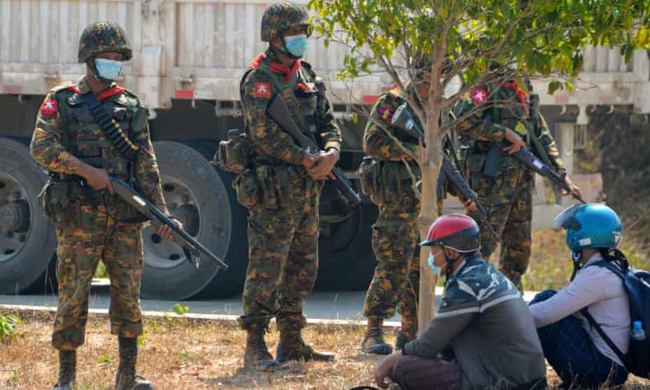 Soldiers stand guard over protesters detained as they blocked a road near a prison in Naypyidaw