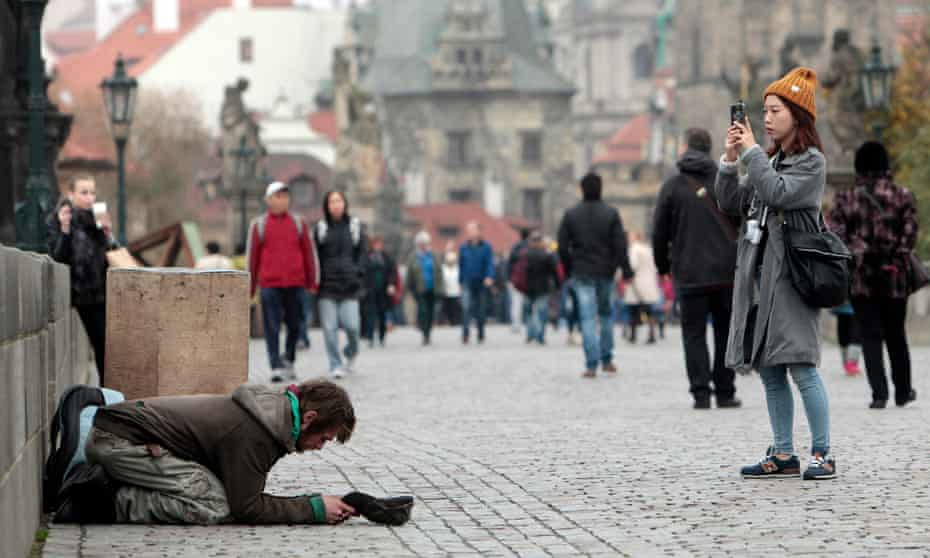 A tourist takes a picture next to a beggar on the Charles bridge in Prague.