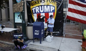 A postal worker collects mail from a mailbox inside the protest pen, as a handful of supporters of Donald Trump demonstrate outside the Pennsylvania Convention Center this week.