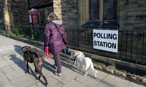A woman walking her dogs past a polling station in Saltburn By The Sea.